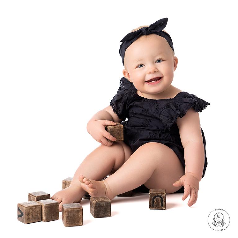 Glad ettåring sitter och leker med klossar i trä.