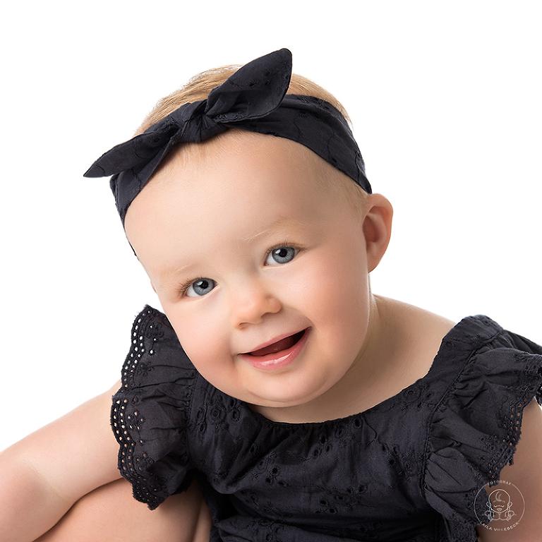 Ett vackert och ärligt porträtt på ettåriga Clara där hon tittar in i kameran och ler vänligt.