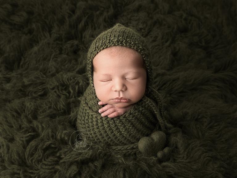 Nyfödd pojke invirad en en härligt murrigt grön stickad filt, placerad på en mörkgrön flokati. Två små hjärtan som går ton i ton med resten av det gröna i bilden pyntar bilden och är placerade i botten av bebisens stickade wrap.