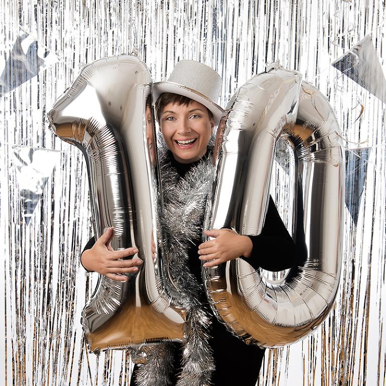 Fotograf Laila Villebeck står med sifferballoner nummer 10, glitterhatt och glitterboa. En glad bild för att fira 10 år som fotograf i Linköping